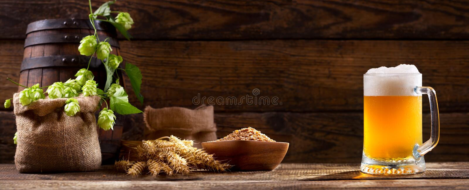 Mug of beer with green hops and wheat ears royalty free stock photo