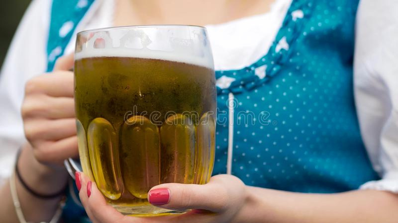 A mug of a beer in a hand oktoberfest stock image