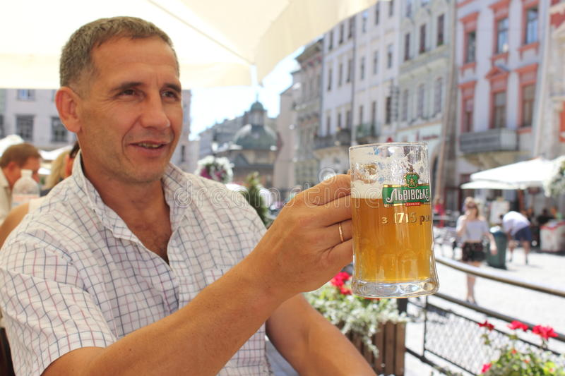Mug of beer Lviv in Lviv. Man holding a glass of beer freshly brewed in his hand. Lvivske - Ukrainian beer brand, produced Lviv brewery since 1715 currently stock photography