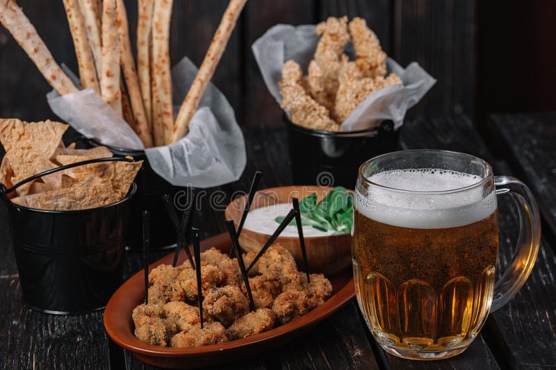 Mug of beer and snacks. Grissini, chicken grilled breast, pita chips, fried chicken hearts, sauce royalty free stock photo