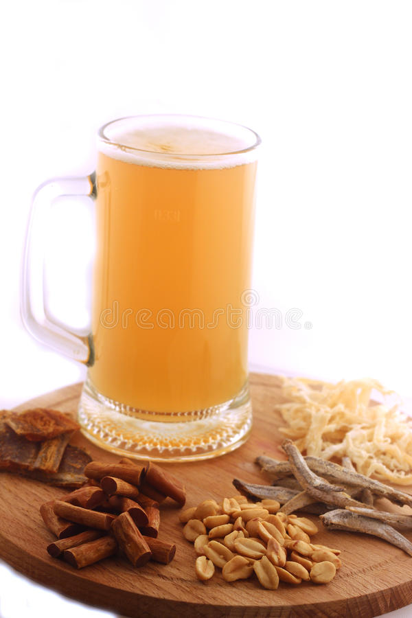 Mug of beer. A mug of beer and snacks on wooden desk stock photos