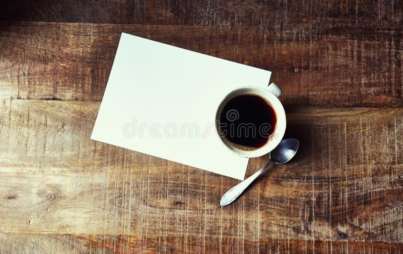 Mug of Black Coffee and a blank paper sheet on rustic wooden table; seen from above stock photos