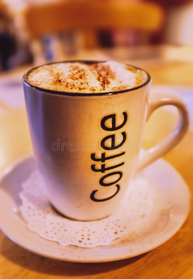 Mug of cappuccino coffee with the word coffee written on the side. On a saucer with a paper lace doily on a round wooden table royalty free stock photo