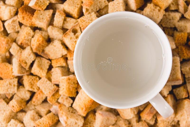 A mug of carbonated water among rusks stock photo