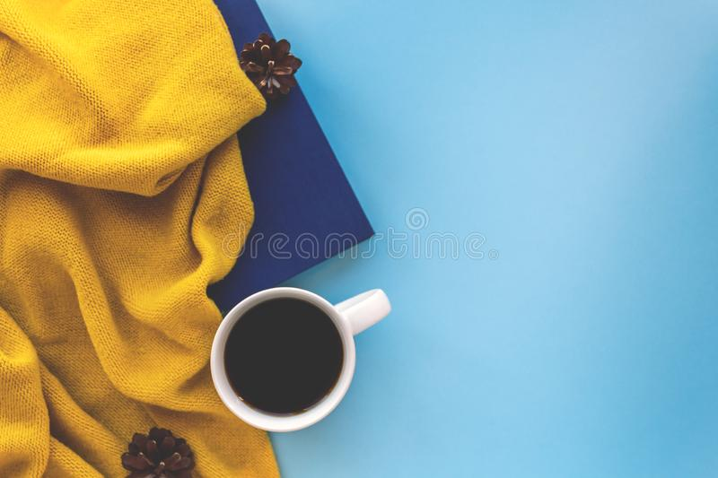 Mug of coffee in autumn flatlay composition. Mug of coffee, book, daily planner, warm scarf and cones on blue background. Autumn flatlay composition in warm royalty free stock photo