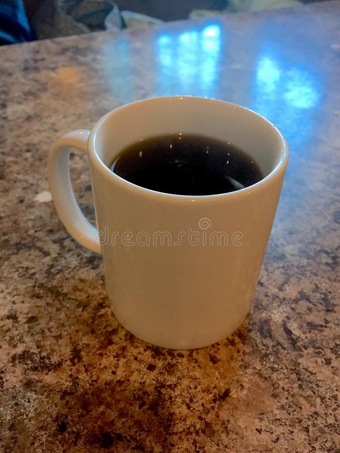 Mug of Coffee on a Restaurant Table. Steaming hot cup of joe on a diner table stock image