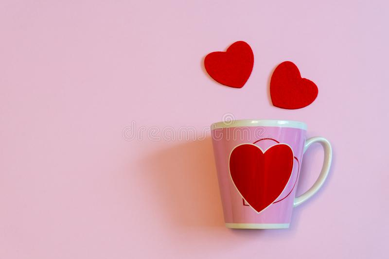 Mug for coffee or tea and two red hearts on pink pastel background. Creative layout in minimal style. Love, romance, Valentine`s stock image