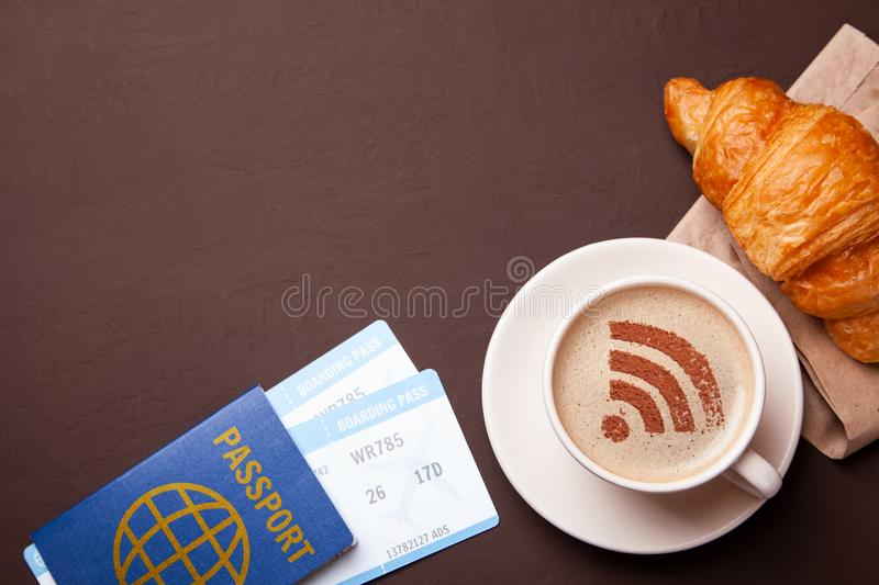 Mug of coffee with WiFi sign on the foam. Free access point to the Internet WiFi. I like coffee break with croissant stock image