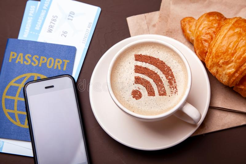 Mug of coffee with WiFi sign on the foam. Free access point to the Internet WiFi. I like coffee break with croissant stock images
