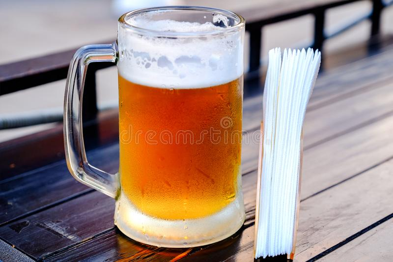 A mug of cold beer, misted droplets roll down the glass. On the table next to the napkin holder with napkins.  stock photo
