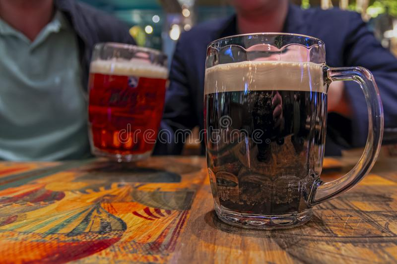 Mug of dark beer on vintage tavern table. Concept of a friendly feast, a fun meeting. Mug of dark beer on vintage tavern table. Concept of a friendly feast, a royalty free stock photography