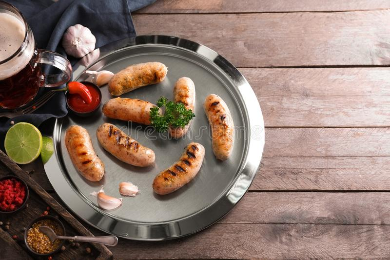 Mug of delicious beer, grilled sausages and fresh sauces on wooden table stock image