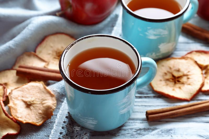 Mug with fresh apple juice, chips and cinnamon sticks on wooden table stock photography