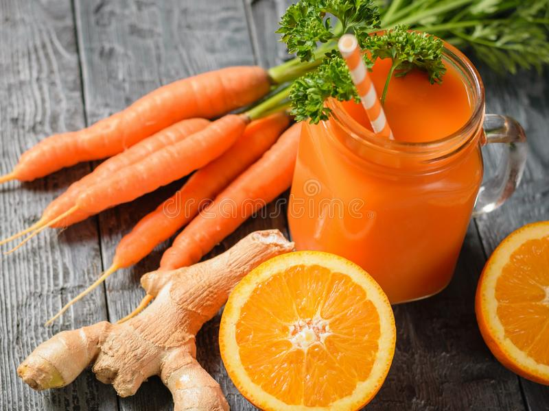 A mug of fresh carrot smoothie with cocktail straw, parsley, ginger root and oranges on a dark wooden table. The concept of healthy eating royalty free stock image