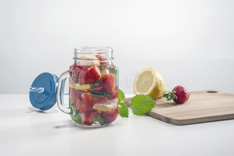 Mug of fruit water with strawberries, mint and lemon, stand on a wooden stand next to fresh strawberries, mint leaf, sliced lemon royalty free stock photo