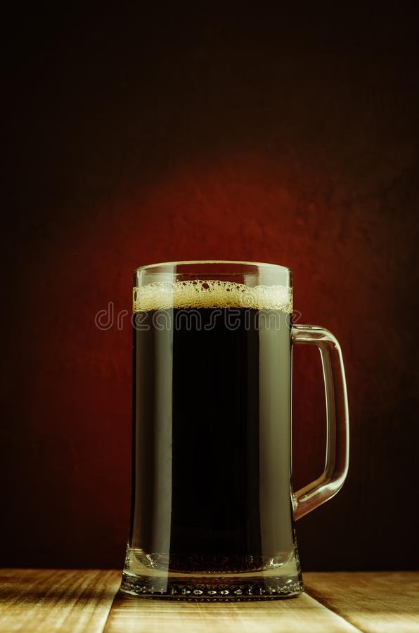 Mug full of beer/mug full of beer on a wooden table and a red background. Bar pub glass alcohol foam pint liquid dark cold drink lager frosty beverage royalty free stock image