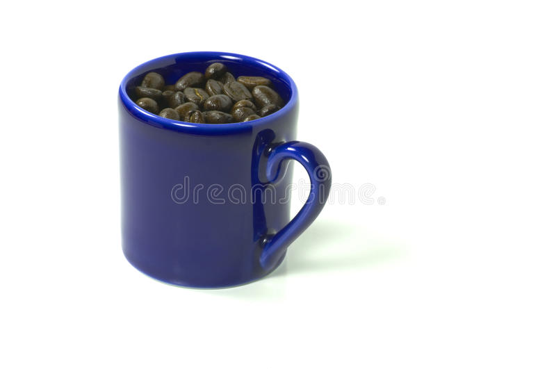Mug full of coffee beans. A blue mug full of coffee beans isolated on white, includes clipping path royalty free stock photo