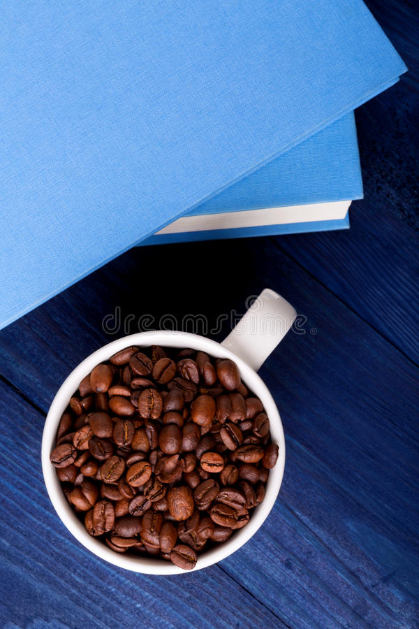 Mug full of coffee beans and two blue books stock photography