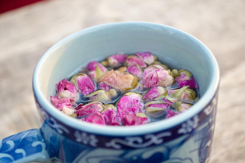 Mug of herbal tea. Herbal tea with flowers. Mug on a wood table (close up stock photos