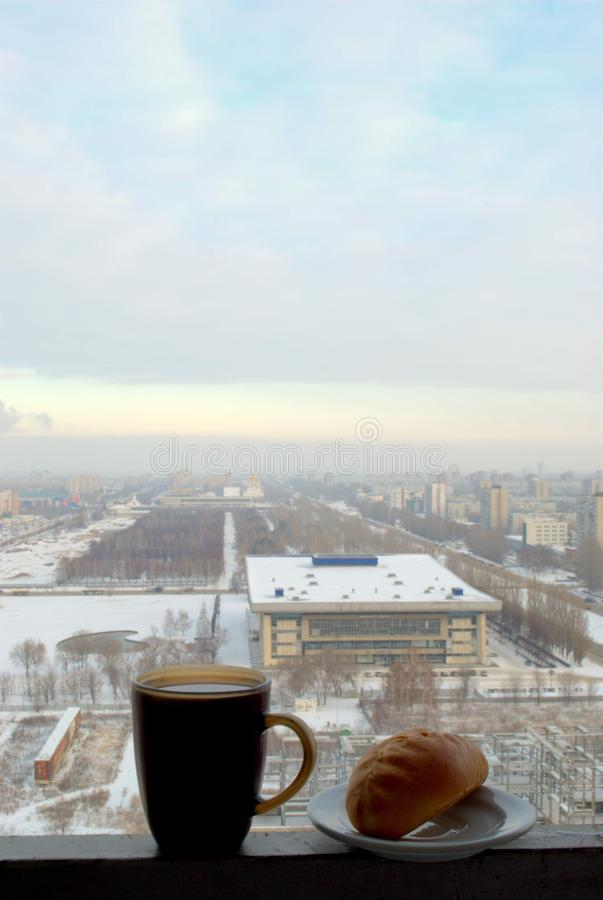 A mug of hot black tea and a fresh ruddy pie against the blurred morning panorama of a winter city. stock photo