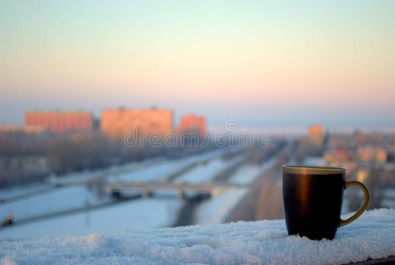 A mug of hot black tea stands on the balcony railing against the background of a frosty winter dawn and a blurred panorama. royalty free stock photo