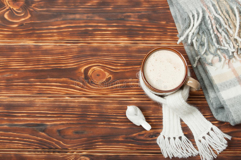 Mug Of Hot Chocolate Or Coffee With Marshmallows. Natural Wool Scarf. Wooden Background With Copy Space royalty free stock photography