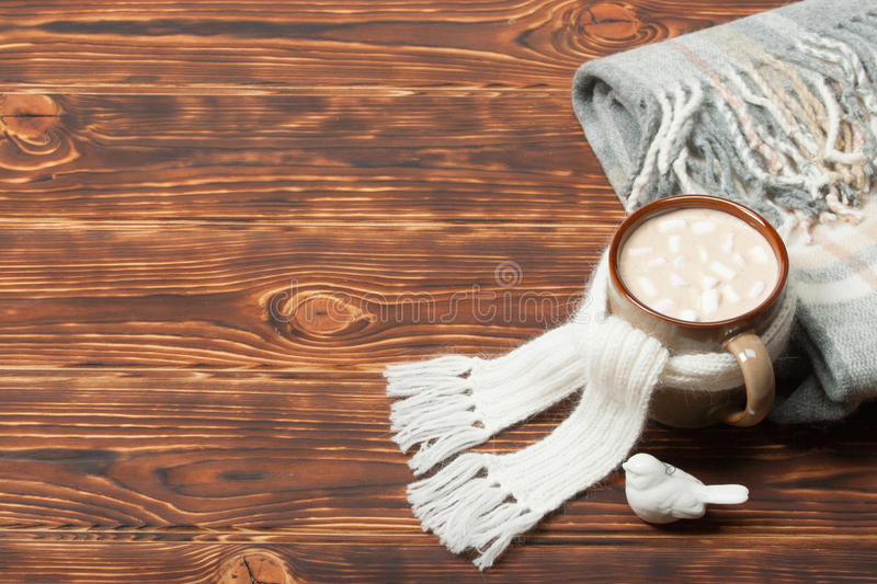 Mug Of Hot Chocolate Or Coffee With Marshmallows. Natural Wool Scarf. Wooden Background With Copy Space stock image