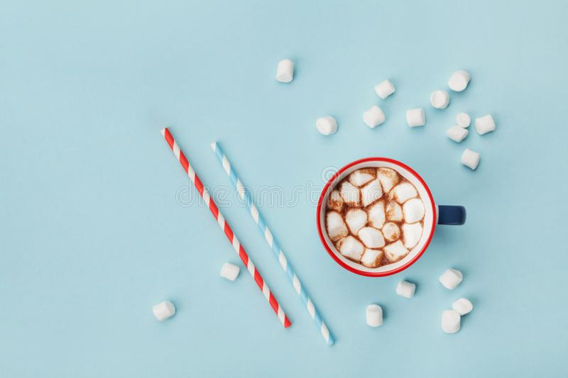 Mug of hot cocoa or chocolate and straw on turquoise table top view. Flat lay. Mug of hot cocoa or chocolate and straw on turquoise table top view. Flat lay stock photo