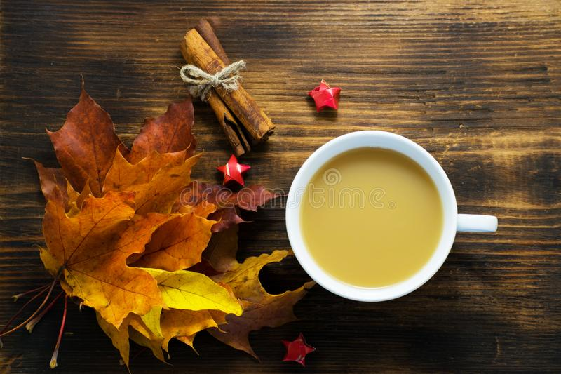 Mug of hot coffee with milk and spices and autumn leaves on wooden table. Morning cup of cappuccino coffee with cinnamon and maple royalty free stock photography