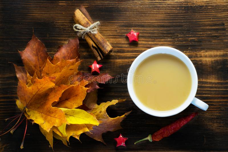 Mug of hot coffee with milk and spices and autumn leaves on wooden table. Morning cup of cappuccino coffee with cinnamon and maple stock photos