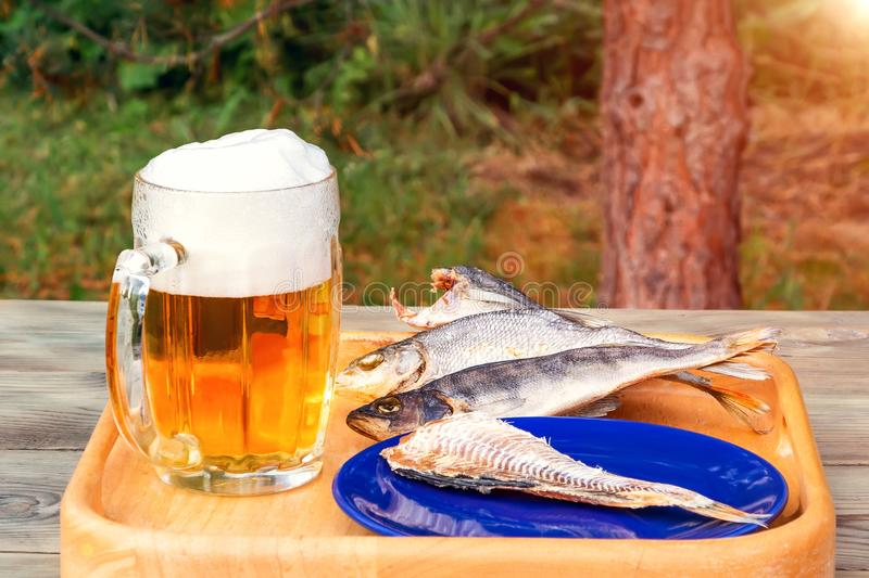 Mug of light beer and dried fish on a wooden table in a summer day outdoors - photo, image stock photography