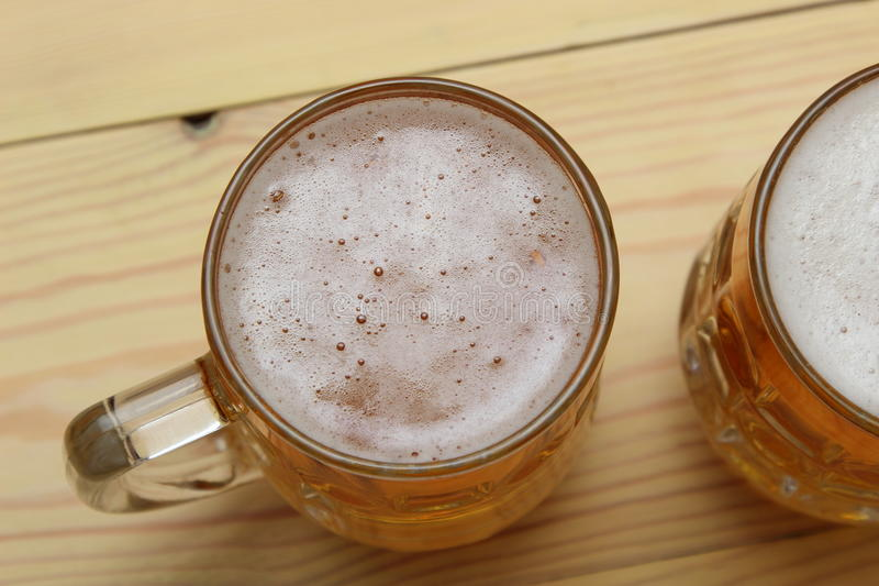 Mug of light beer on the table. Mug of light beer on a table made of wood stock image