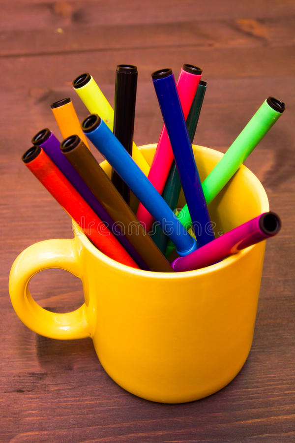 Mug with markers on wood close up view. Cup with markers on a wooden table close up view royalty free stock photo