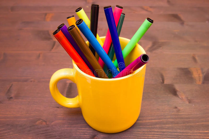 Mug with markers on wood. Cup with markers on a wooden table royalty free stock images
