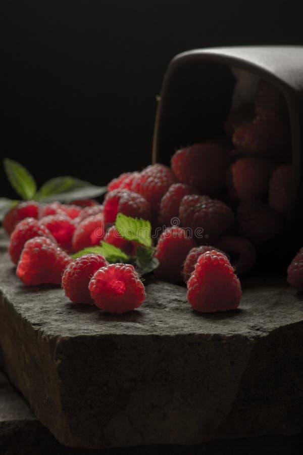Mug of ripe raspberries on black background. royalty free stock photos