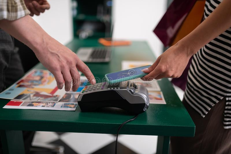Mug shot of female attaching smartphone to credit card terminal stock images