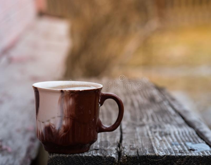 Mug stands on a wooden old bench in the open air. Autumn royalty free stock image