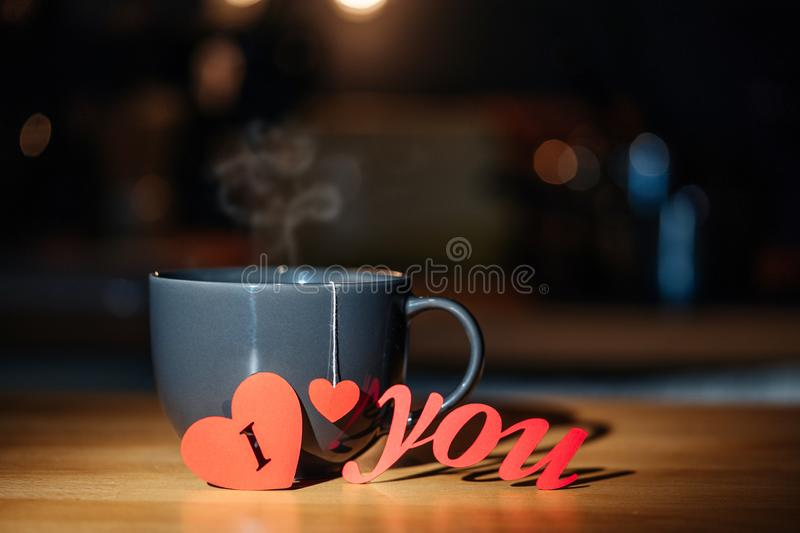 Mug with tea or coffee and cut out of red paper heart symbol and the words I LOVE YOU. Festive composition for Valentine`s Day stock photos