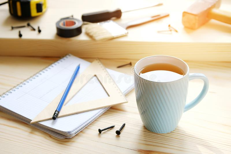 Mug of tea, drawings and construction tools for building a house or apartment renovation, on a wooden table. The workplace of the stock photos