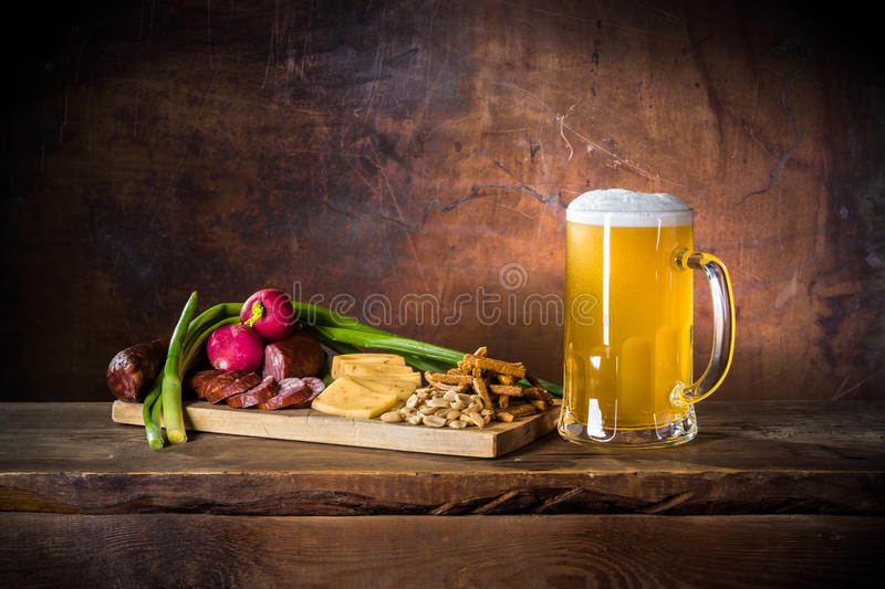 Mug of unfiltered beer and rustic dinner in pub royalty free stock photography