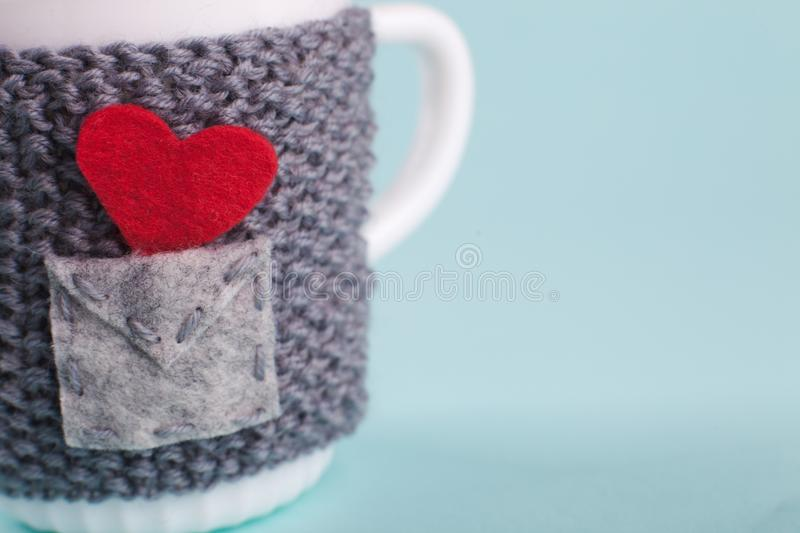 A mug wrapped in a warm cover - an envelope with a message of love, a Valentine`s day, a concept of congratulations. Macro. Copy space stock photos