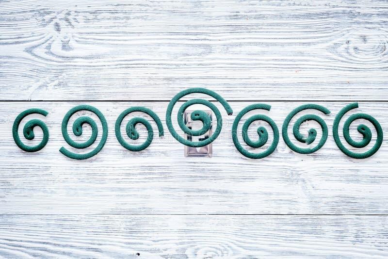 Mugafweermiddel voor openlucht: tuin, de zomerhuis, picknick Groene spiraal op de grijze houten ruimte van het achtergrond hoogst stock afbeelding