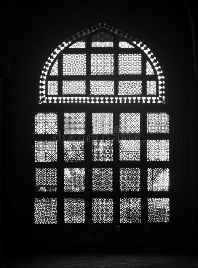 Mughal architecture motif work in black and white. The image belongs to The Tomb of Muhammad Ghaus in Gwalior, Madhya Pradesh, India. It depicts a window inside stock photography