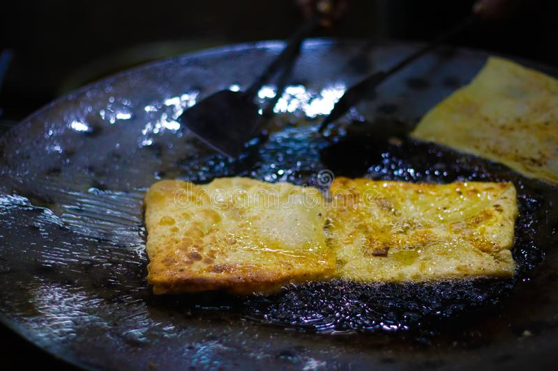 Mughlai paratha, an indian street fast food is being fried in oil in a frying pan.  royalty free stock photos
