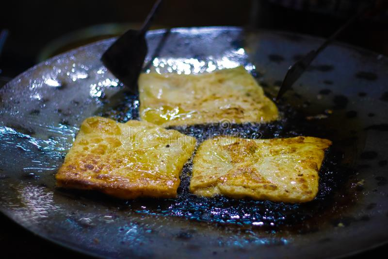 Mughlai paratha, an indian street fast food is being fried in oil in a frying pan.  royalty free stock images
