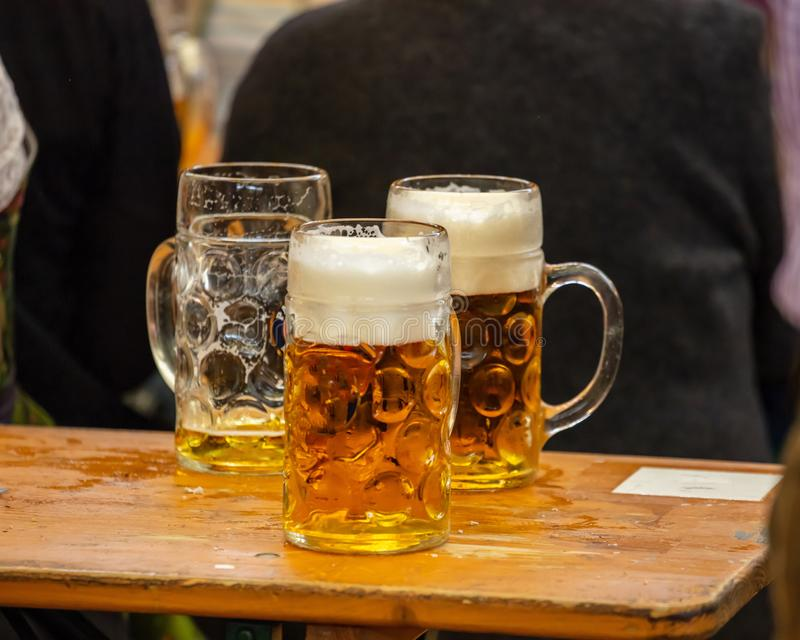 Mugs of beer on a wooden table, closeup view. Oktoberfest, Munich, Bavaria. Mugs of Bavarian beer on a wooden desk, closeup view. Oktoberfest, Munich, Germany stock photos