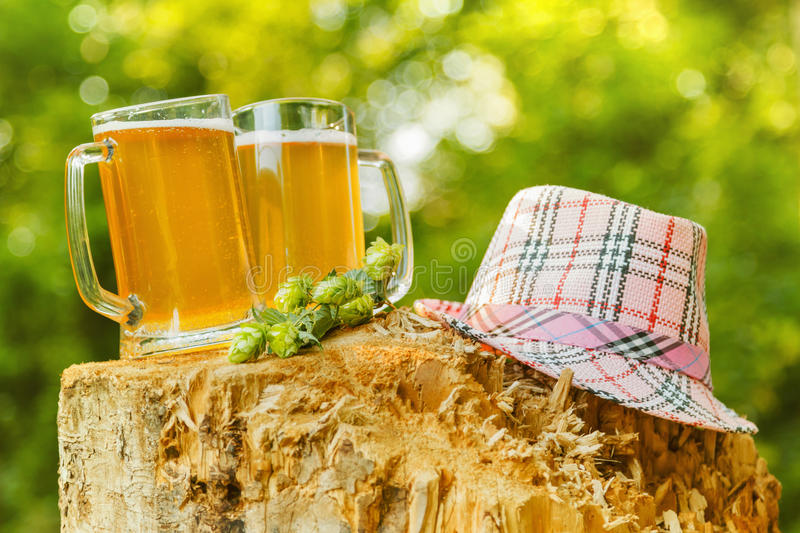 Mugs with beer on natural background. Mugs with beer hops octoberfest picnic on natural background with hat stock photo