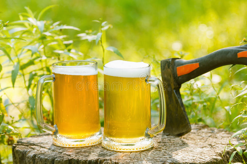 Mugs with beer on natural background. Mugs with beer octoberfest picnic or party on natural background with axe royalty free stock image