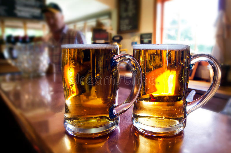 Mugs of beer. WANAKA, NZ - JAN 17:Mugs of beer on pub desk on Jan 17 2014.The global beer industry is forecast to have a value of $496.6 billion in 2014 royalty free stock photo
