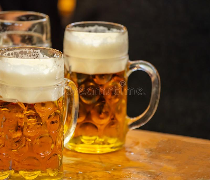 Mugs of beer on a wooden table, closeup view. Oktoberfest, Munich, Bavaria. Mugs of Bavarian beer on a wooden desk, closeup view. Oktoberfest, Munich, Germany stock photography